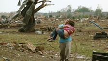 A woman carries a child through a field near the collapsed Plaza Towers Elementary School in Moore, Oklahoma
