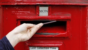 A woman posts a letter into a post box