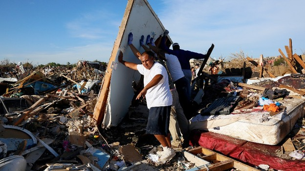 Men lift a wall in an effort to salvage belongings from their tornado-ravaged homes in Moore.
