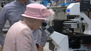 Queen looks down a microscope