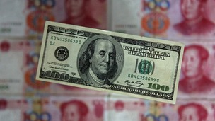 The US dollar displayed in front of the yuan banknotes.