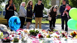 People gather around the floral tributes to Lee Rigby