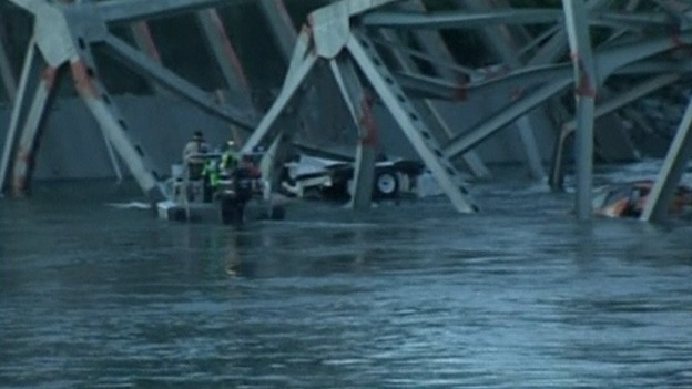 Rescue workers examine two cars submerged in water after the bridge collapse.