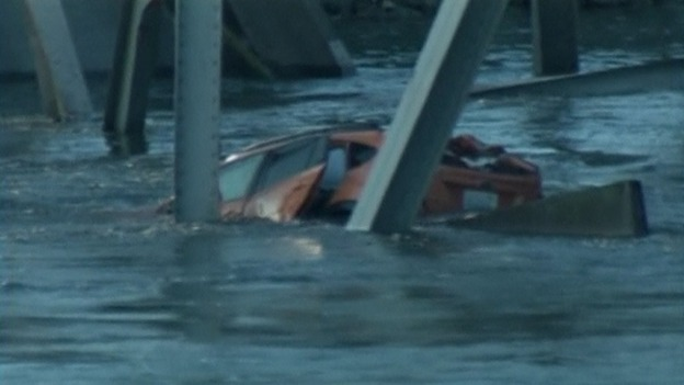 One car can be seen pushed against the girders in the water.