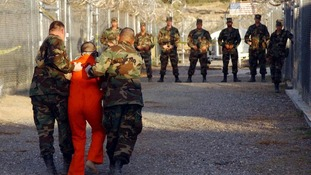US Army Military Police escort a detainee to his cell at Guantanamo Bay.