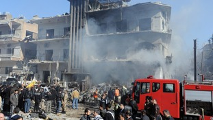 Syrian security members inspecting damaged building after explosions near the intelligence forces in Damascus, March 17, 2012.