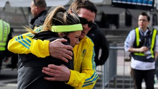 A woman is comforted by a man near a triage tent set up for the Boston Marathon