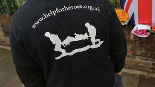 Men wearing Help For Heroes clothing leave flowers at the scene