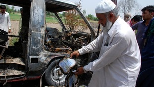 A man displays a burnt book to the media near a burnt-out school bus on the outskirts of Gujrat