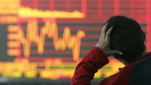 An investor looks at an electronic board showing stock information
