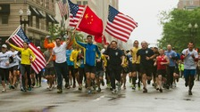 Runners carry American and Chinese flags as they approach the finishing line.