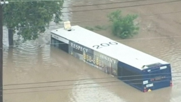 A bus is half submerged under the flood water