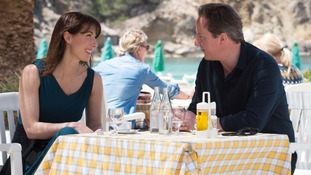 Prime Minister David Cameron and his wife Samantha take a drink by a beach