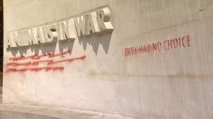 The words on the memorial have been crossed out in red spray paint