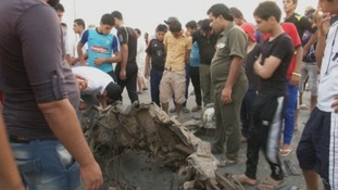 Baghdad residents inspect a piece of twisted metal close to one of the blasts
