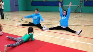 Beth Tweddles shows children in Newquay exercises.