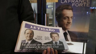 A newspaper seller displays an early edition of Le Figaro