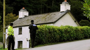 Police outside the cottage Mark Bridger was renting in Ceinws at the time of April's disappearance