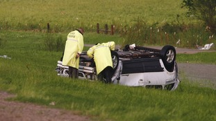 Oklahoma Highway Patrol staff look at a flipped vehicle, which was blown off of Interstate-40, killing a mother and child.