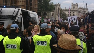 Police hold back protesters outside parliament.