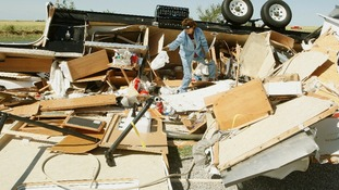 Mikie Hooper of Tuttle, Oklahoma, collects her belongings from the wreckage of her trailer.