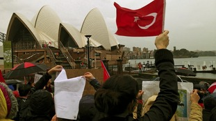 Turkish protesters hold banners and Turkish national flags on the steps of the Sydney Opera House.