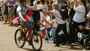 A cyclist gets some support from the waiting crowd.