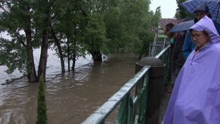 A tourist surveys the flooded River Vltava