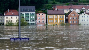 street sign is partially submerged in the flooded centre of the Bavarian town of Passau,