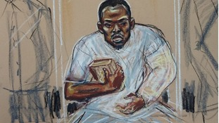 Michael Adebolajo sits in the dock holding a copy of the Koran.