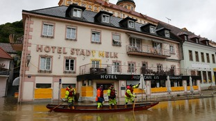 Emergency workers travel by boat along a flooded street in the centre of the Austrian town of Melk
