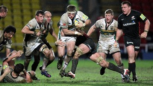 Northampton's Alex Waller (centre) is tackled by Saracens Steve Borthwick