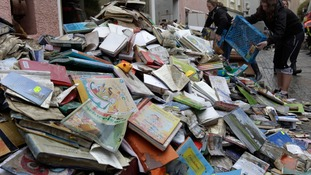 Mud covered books are placed outside a book shop in the town of Passau in Germany