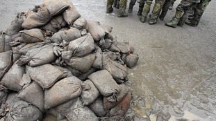 Members of the German army stand in the mud next to sandbags in Passau