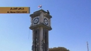 A soldier plants a Syrian flag atop a clock tower in the western town of Qusair