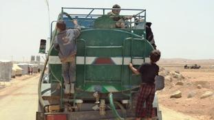 Children hitch a ride on a water truck in the Zaatari refugee camp