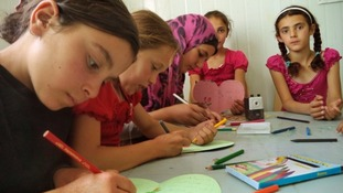 Children drawing in an activity centre at the camp