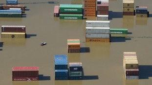 Shipping containers partly immersed in water at the flooded harbour in Riesa