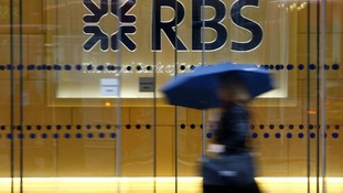 A woman walks past the headquarters of the Royal Bank of Scotland in the City of London with an umbrella.