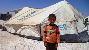 Suleiman stands in front of his family tent in Zaatari refugee camp