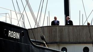 Duke of Edinburgh (left), stands aboard the SS Robin