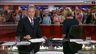 Sophie Long turns around to see the Queen surrounded by a crowd in the newsroom.