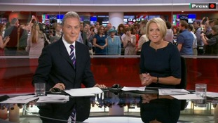 The BBC News presenters seem unaware that the Queen is behind them during their broadcast.
