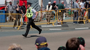 A policeman runs to aid injured spectators at TT