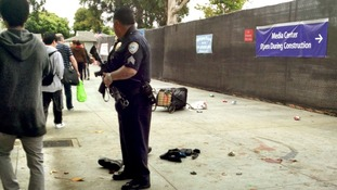 A policeman stands guard over the scene where a man believed to be the suspect in a shooting incident at Santa Monica College