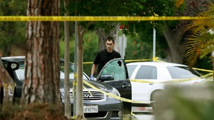 A police officer is seen by a bullet riddled car