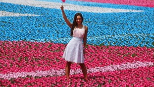 Myleene Klass stands with one of 250,000 flowers with eight petals