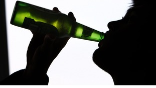 A man swigs from beer bottle