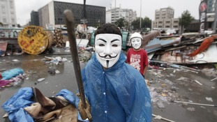 A boy wearing a Guy Fawkes mask displays his wooden sword in Gezi Park in central Istanbul