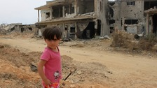A child in front of a damaged house in Qusair